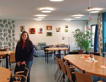 Feierwerk_Blog_Nachbarschaftstreff_NBT_Sylvie_allein_im_Gruppenraum_Hintergrund_Eingang_Treppenhaus